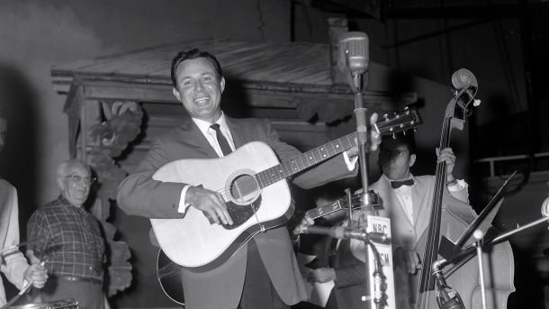 Jim Reeves on the Grand Ole Opry, September 3, 1960 . Classic photo: Reeves is smiling, resting weight on left leg, and extends other foot so it looks as though he's walking. Gray-haired man in window-pane shirt is Opry stage manager and WSM libraria